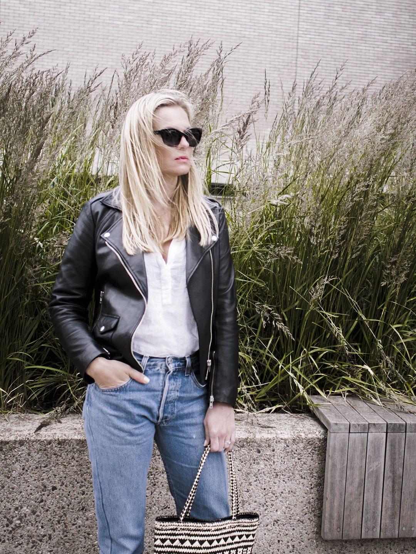 Vikki wears The White Company Linen Blouse, Levi 501s, Straw Bag, Ace & Tate black sunglasses and Sandro biker jacket