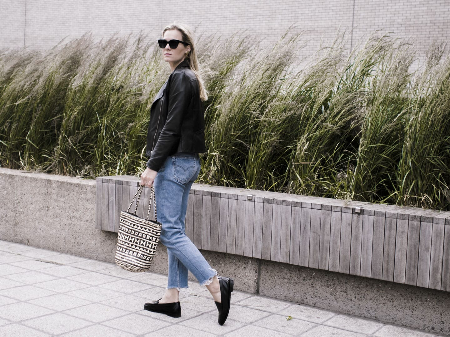 Vikki wears Levi 501s, Bass Weejun black loafers, straw bag, Sandro biker jacket and Ace & Tate black sunglasses