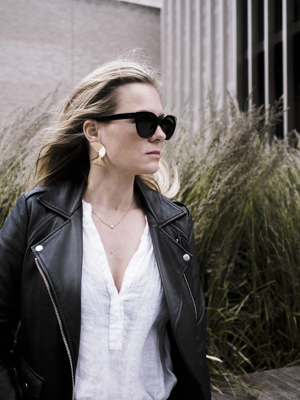 Vikki wears The White Company linen blouse, Sandro biker jacket, Finery statement earrings and Ace & Tate statement earrings