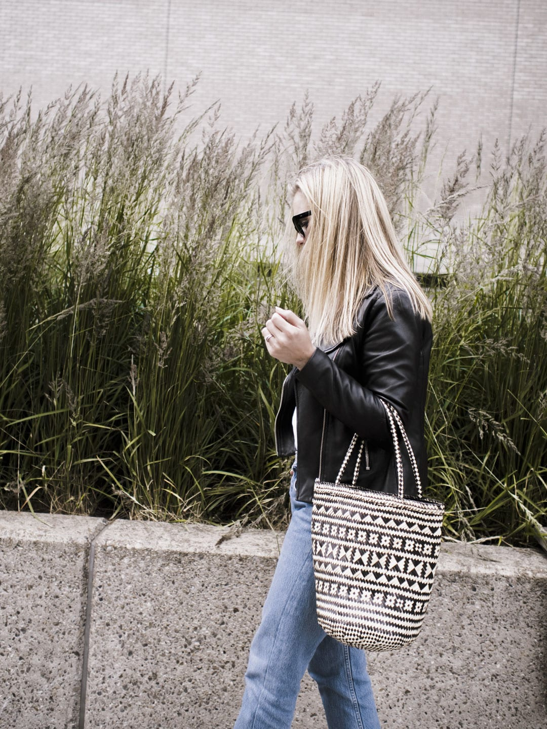 Vikki wears Levi 501s, Bass Weejun black loafers, straw bag, Ace & Tate black sunglasses and Sandro biker jacket