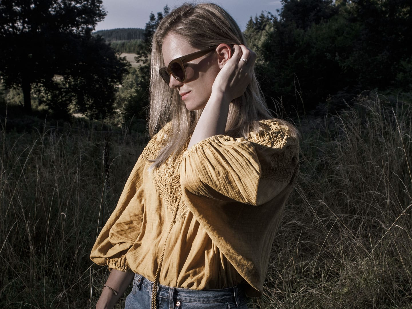 Photo of woman wearing yellow boho peasant top & retro sunglasses in French field