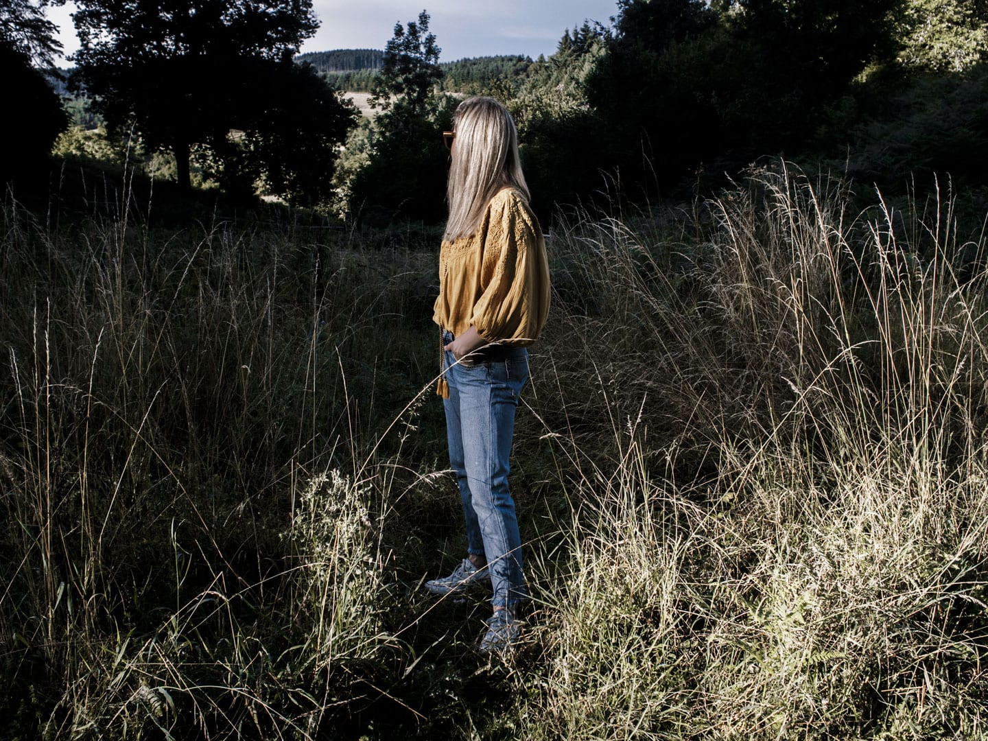 Photo of woman facing away wearing yellow boho peasant top, Levi 501s & Converse plimsolls in French field