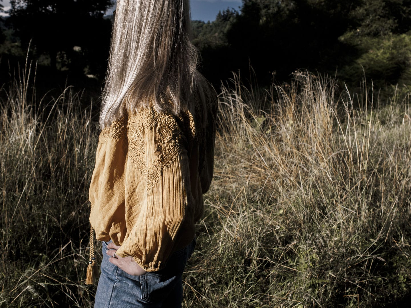 Photo of woman facing away wearing yellow boho peasant top & Levi 501s in French field
