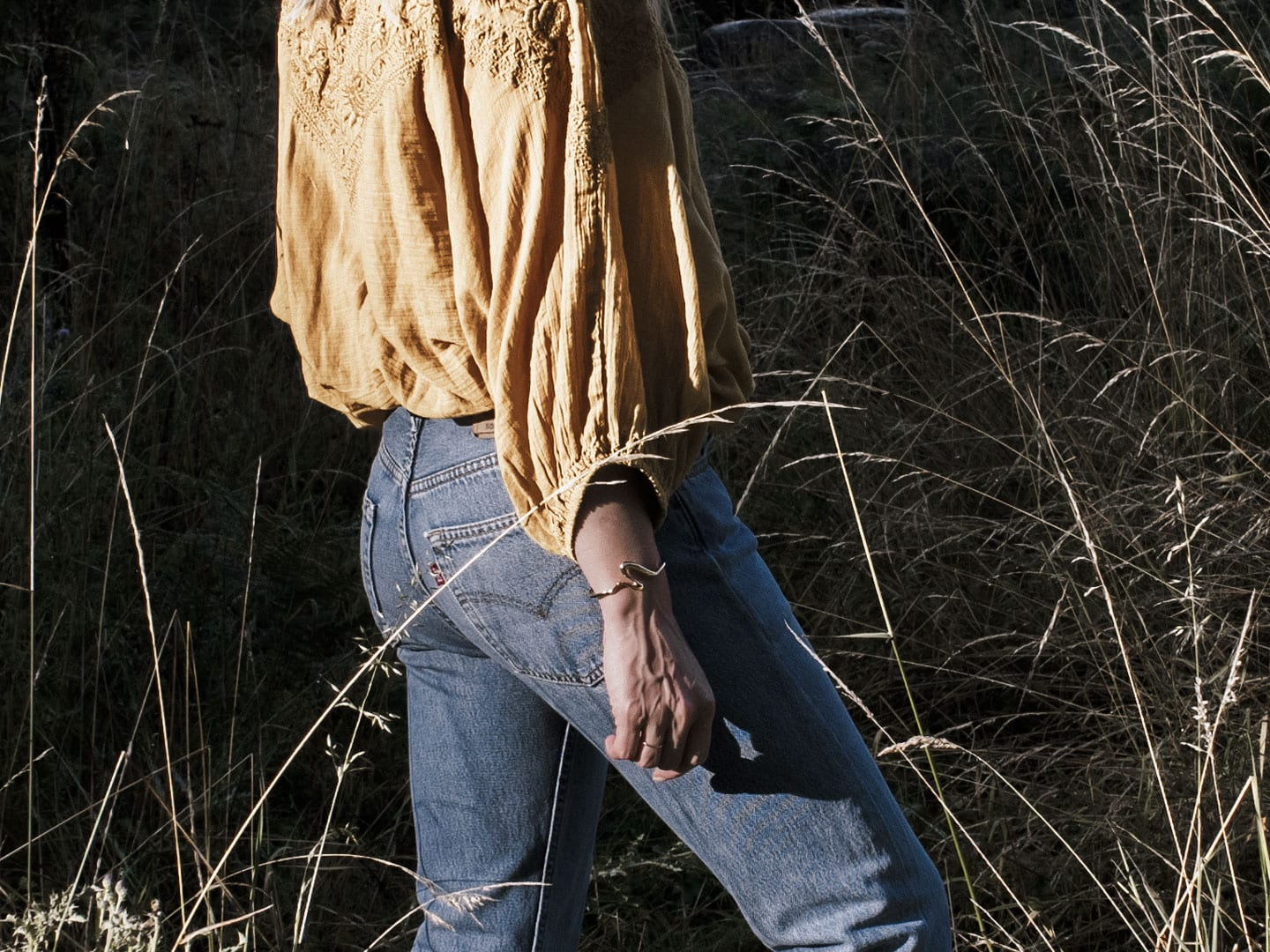 Photo of woman wearing yellow boho peasant top & Levi 501s in French field