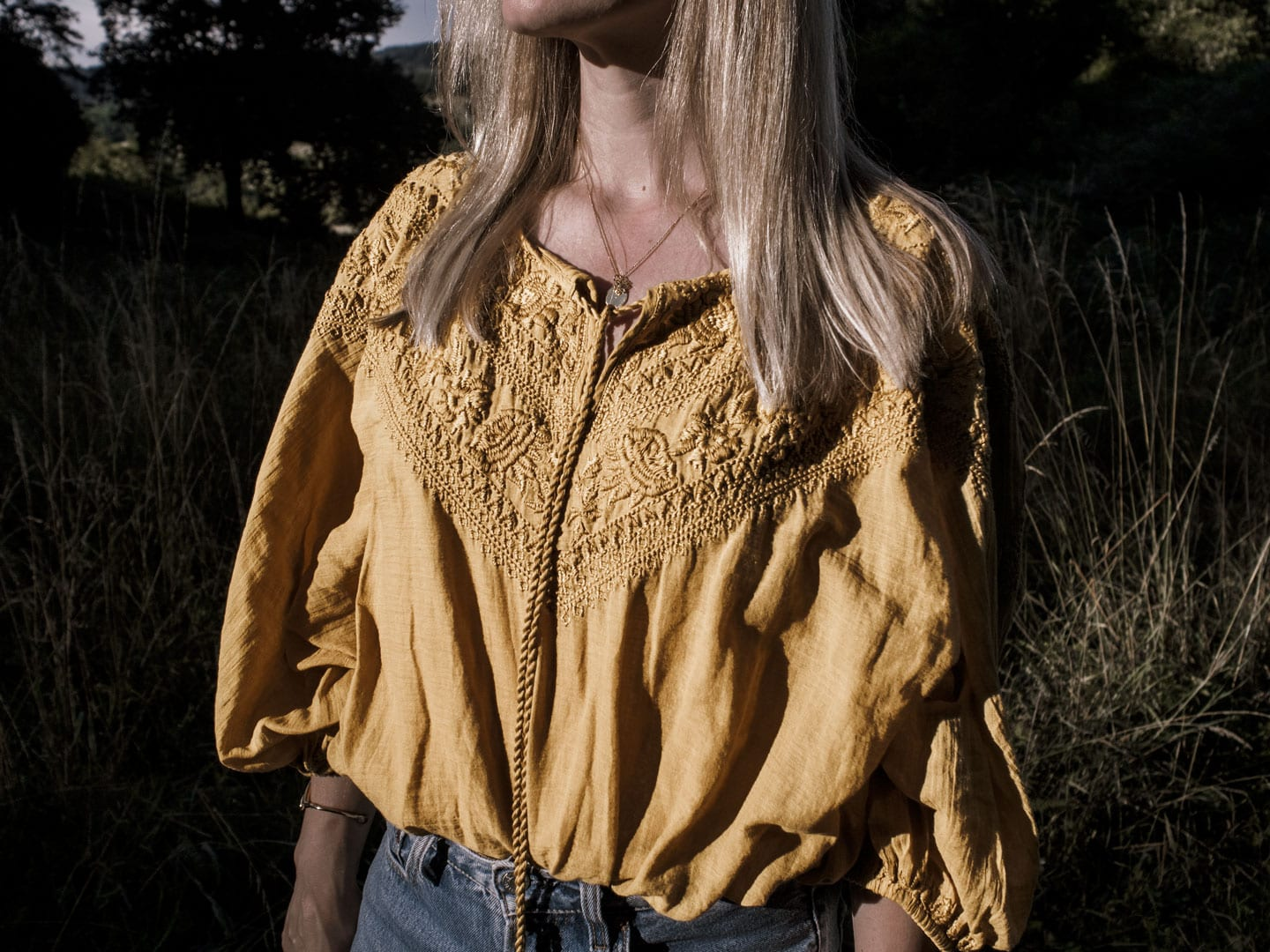 Photo of woman wearing yellow boho peasant top in French field