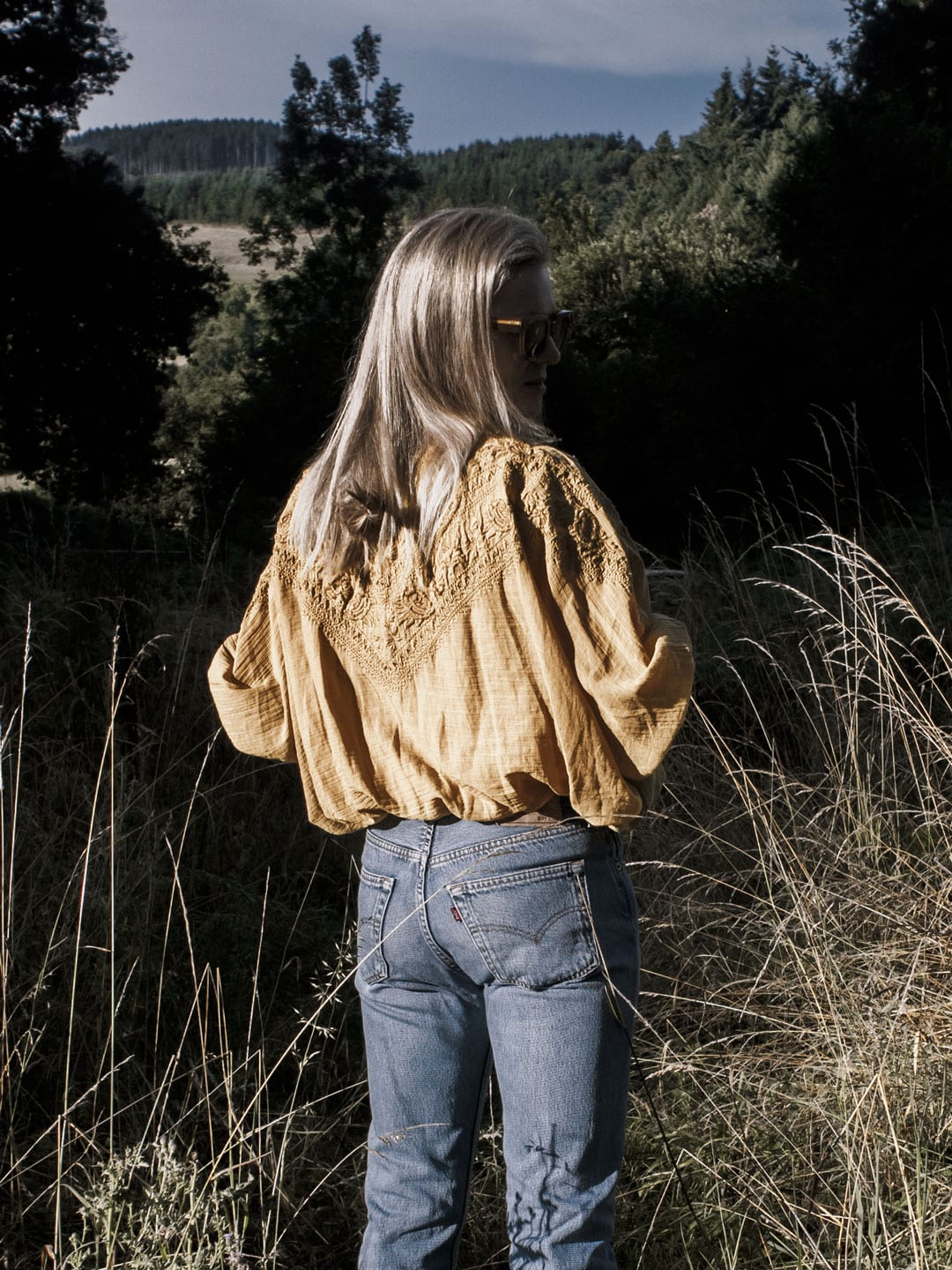 Photo of woman wearing yellow boho peasant top, Levi 501s & Converse plimsolls in French field