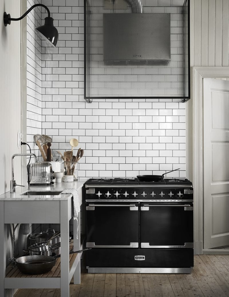 White tiled kitchen with black stove | Home of Artilleriet's Owners